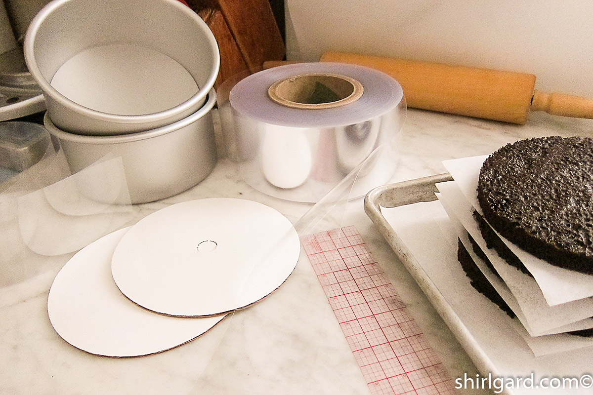 """Tools for assembling Brooklyn Blackout Cake: Two cake pans, 3"""" (7.5 cm) wide acetate cake band, 2 cake boards, & C-thru ruler."""