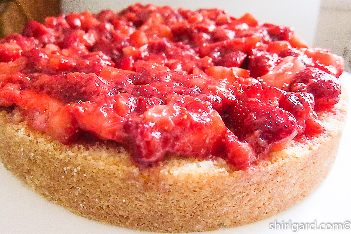 Crushed strawberries added to bottom layer of cake & quartered berries